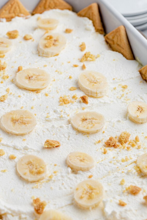 Sliced bananas and cookie crumbs on top of Cool Whip.