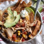 Chicken Tortilla Soup garnished with avocado, chips, sour cream, and lime