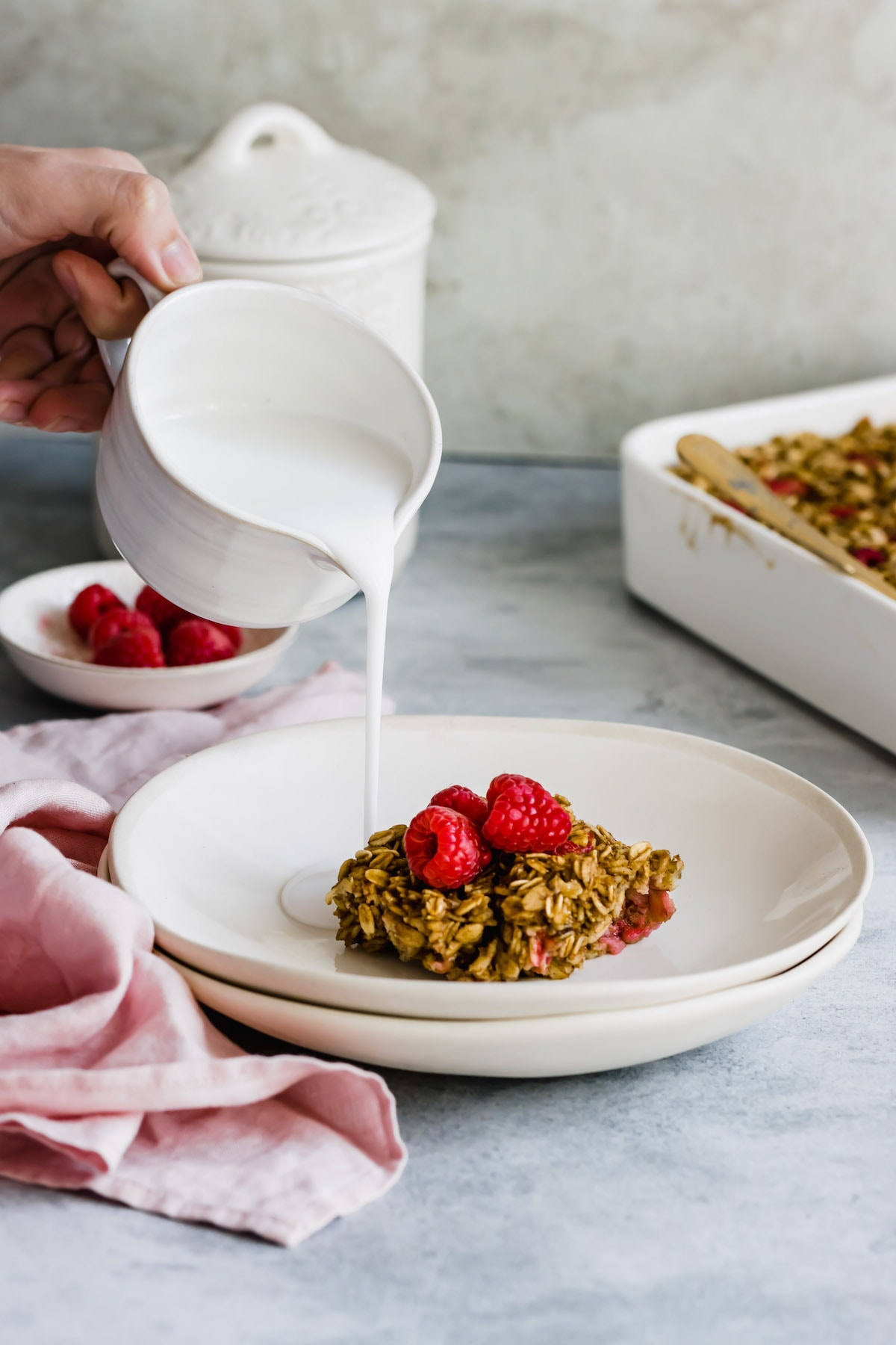 Milk poured over raspberry baked oatmeal.