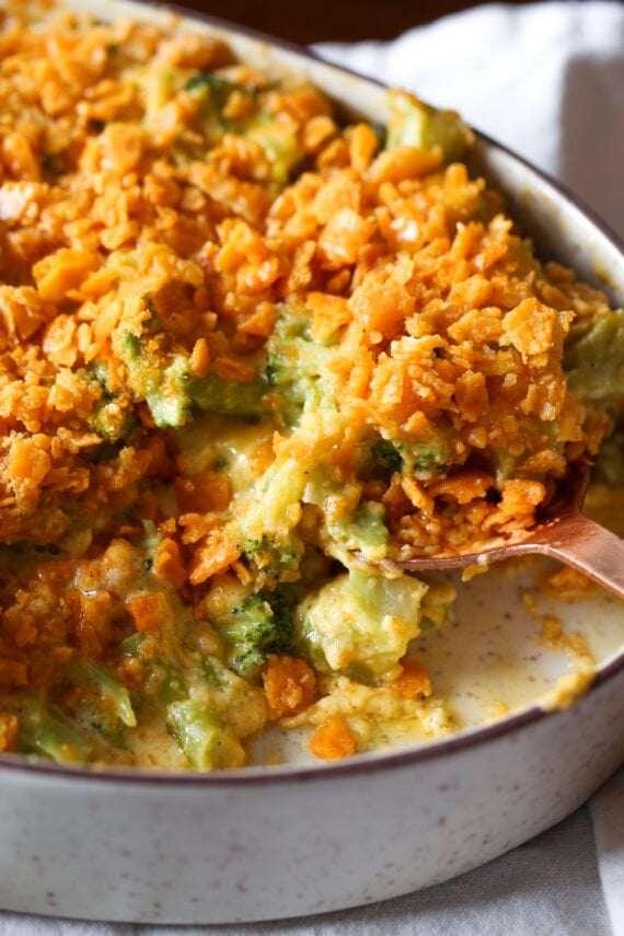 Scooping out broccoli casserole in a baking dish