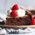 Flourless Chocolate Cake topped with whipped cream and raspberries