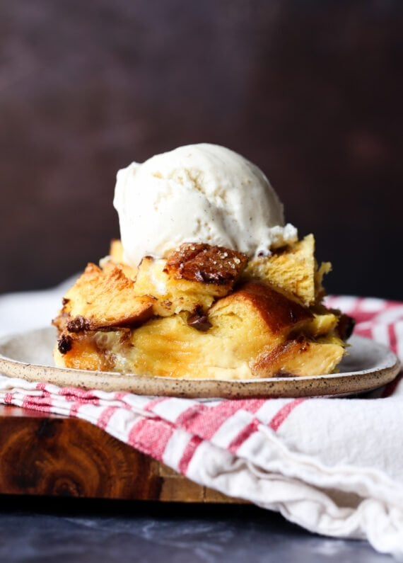 bread pudding baked and plated then topped with a scoop of vanilla ice cream