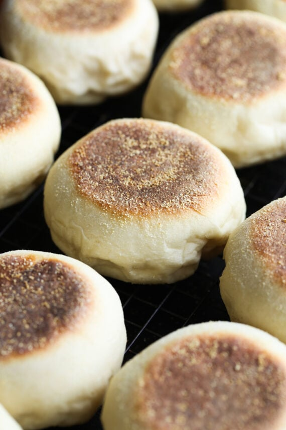 Homemade English muffins cooling on a rack