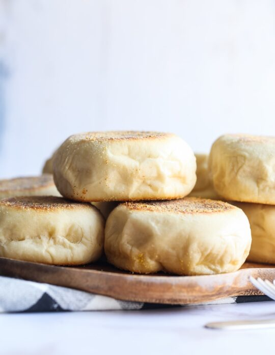 Homemade English muffins stacked on a plate