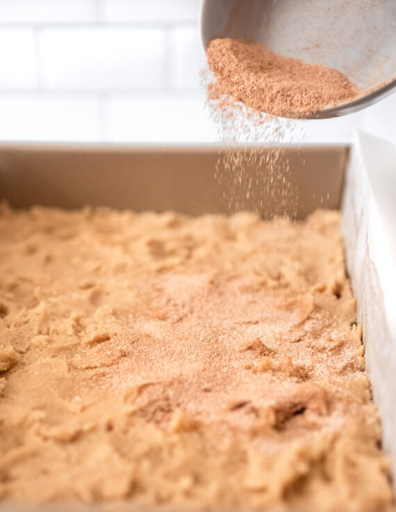 Sprinkling cinnamon sugar on cookie bars