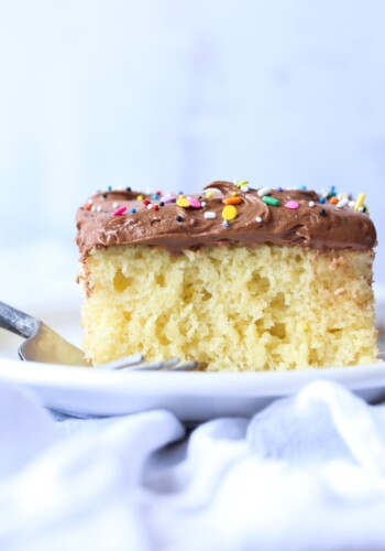 Vanilla cake with chocolate frosting and rainbow sprinkles on a white plate with a fork.