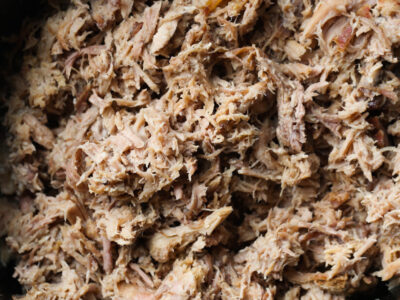 Shredded pulled Kalua pork in a crock pot.