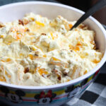 A bowl of orange cream fruit salad topped with chopped pecans ready to be served.