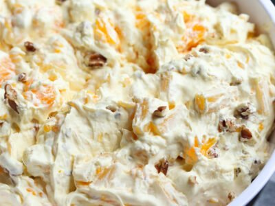 A close up image of bowl of orange cream fruit salad topped with chopped pecans.