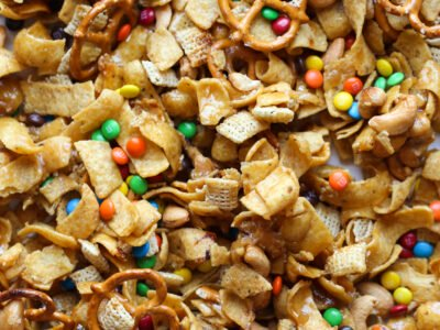 Frito Snack mix on a baking sheet with M&Ms, Fritos, pretzels, and chex cereal