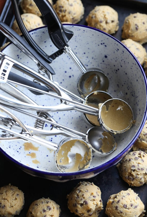 Cookie Scoops in a Bowl Surrounded by Cookie Dough Balls