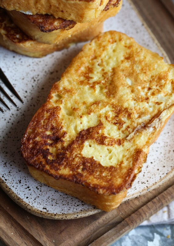 A Slice of Super Fluffy French Toast on a Speckled Plate