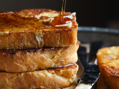Pouring Maple Syrup over a Stack of Brioche French Toast