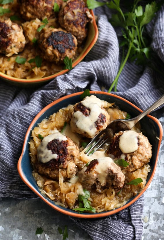 Two Bowls of German Meatballs with Mustard Gravy Drizzled Over One of Them