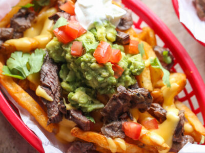 Carne Asada French Fries topped with guacamole, cheese sauce, and sour cream in a basket