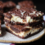Two Cheesecake Brownies Stacked on a Plate With a Bite Taken From the Top One