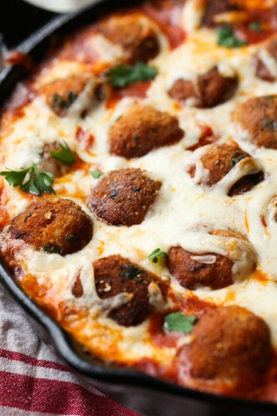Breaded Chicken Meatballs in marinara sauce baked in a skillet topped with cheese