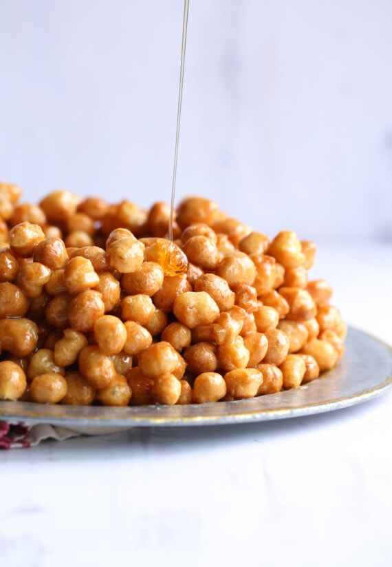 Struffoli Being Drizzled with Honey on a Gold-Rimmed Plate