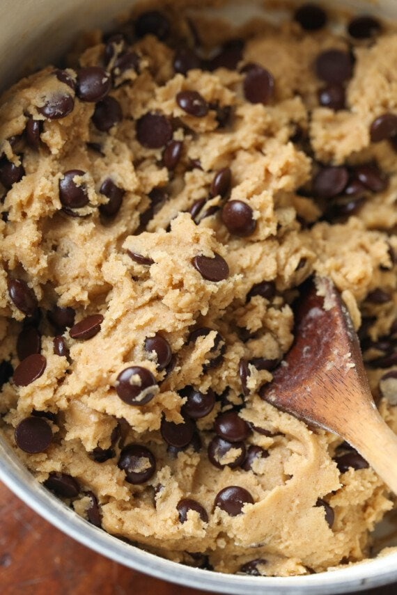 chocolate chip cookie dough with a wooden spoon
