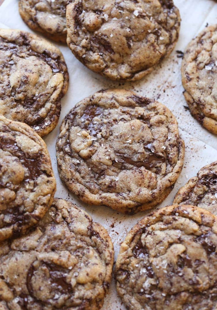Chocolate chip cookies topped with sea salt on white parchment paper.