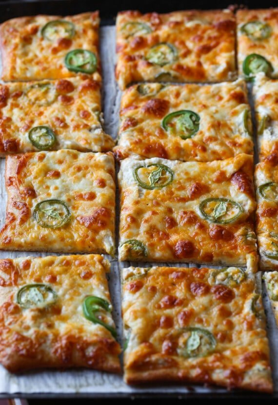 jalapeno pizza on a baking sheet sliced
