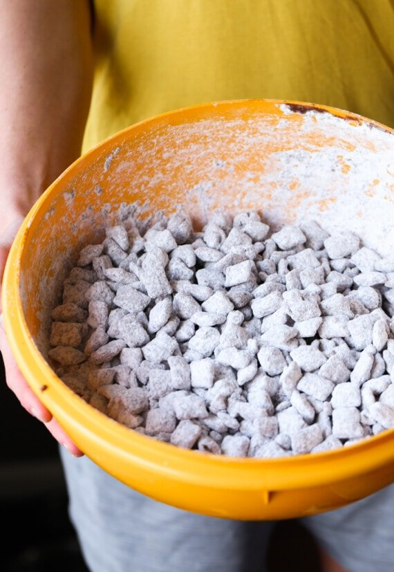 Shaking Puppy Chow with powdered sugar in a large bowl