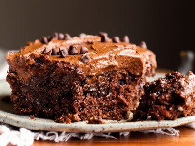 Poke Cake topped with chocolate frosting with a fork