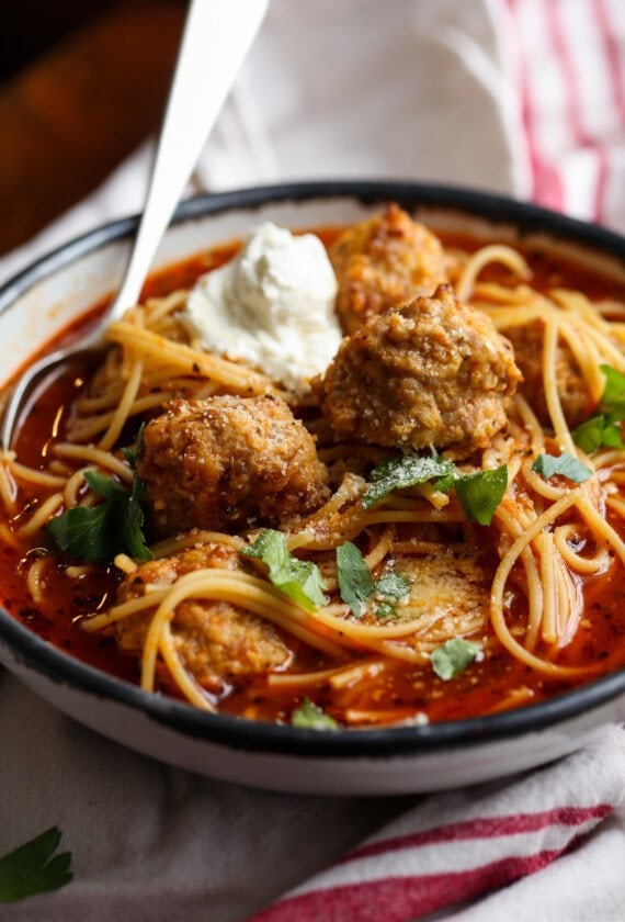 Spaghetti and Meatball soup in a bowl with ricotta cheese and parsley