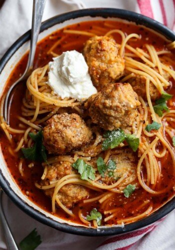Bowl of spaghetti and meatball soup topped with parmesan cheese and ricotta