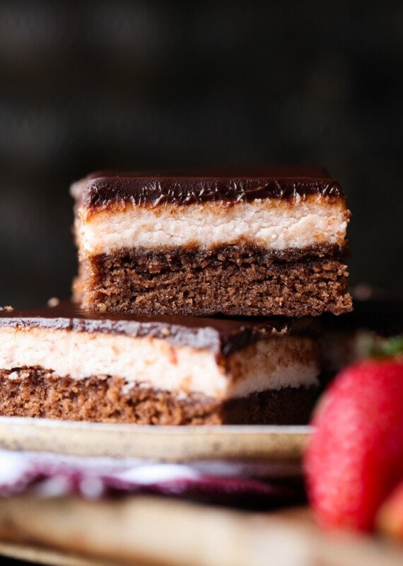 Brownies layered with strawberry frosting and chocolate ganache stacked on a plate