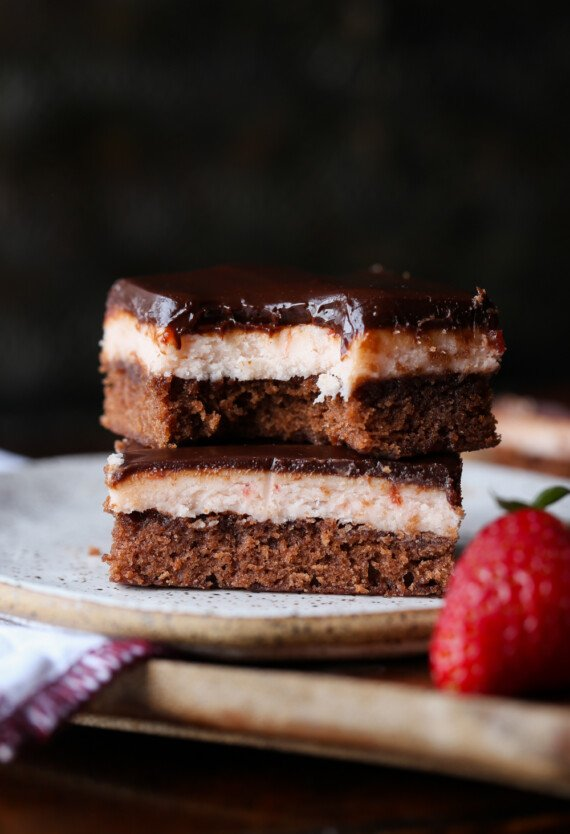 Strawberry Brownies stacked on a plate with a bite taken out