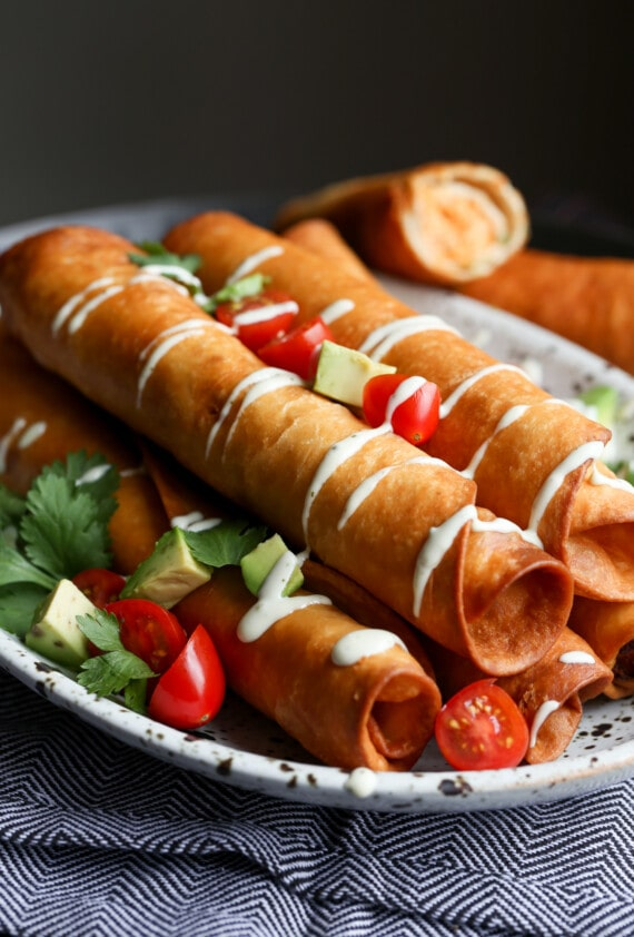 Chicken flautas with a sour cream drizzle on a platter