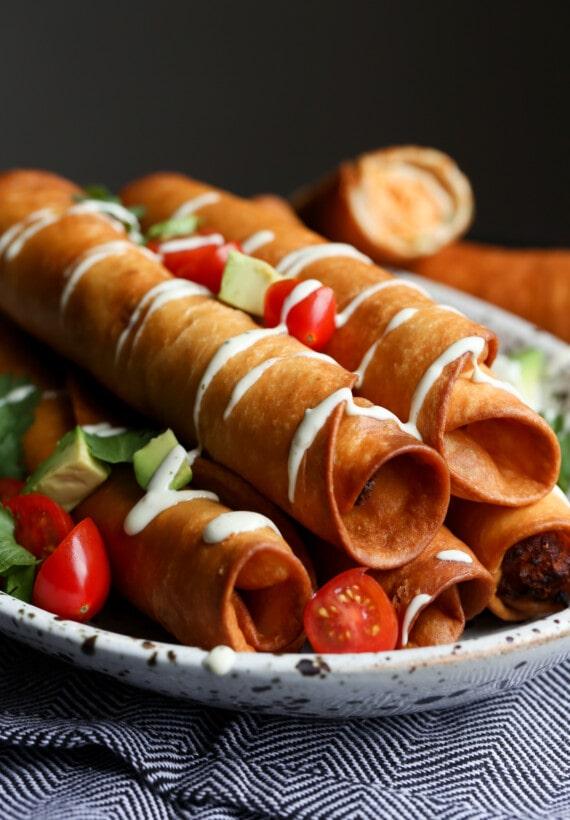 Flautas de Pollo stacked on a platter