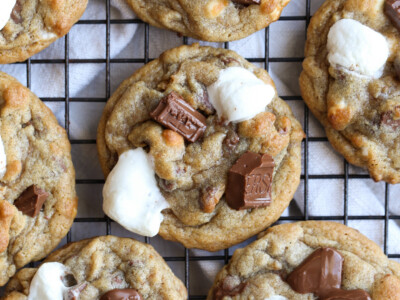 S'mores Cookies on a cooling rack with mini marshmallows and Hershey's chocolate