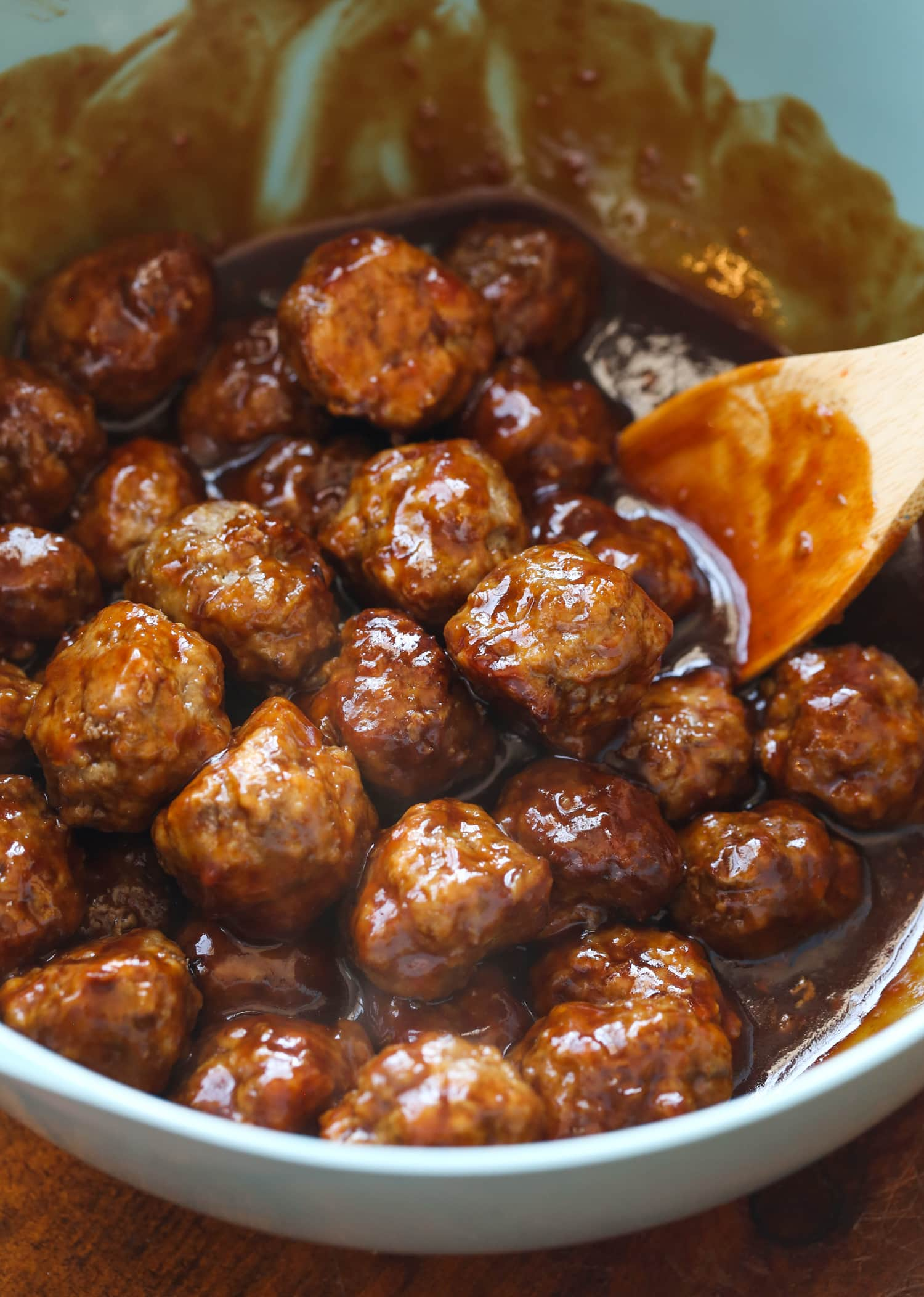 Sesame meatballs being mixed with a wooden spoon.