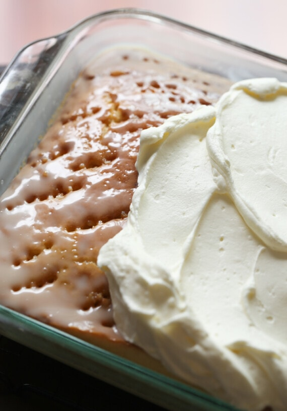 Poke cake being frosted with whipped topping