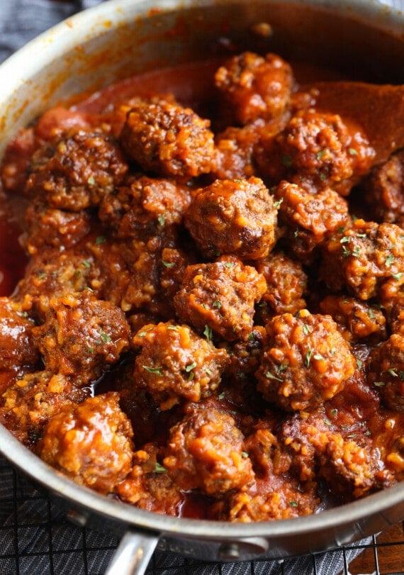 Porcupine meatballs simmering in a saucepan.