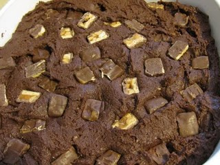 The Batter for Cake Mix Snickers Brownies with Snickers Pieces Pushed Into It