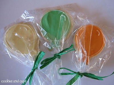 Individually Packaged Yellow, Green and Orange Balloons Lined Up on a White Surface