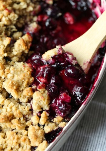 Blueberry Crisp in a baking dish with a spoon to serve