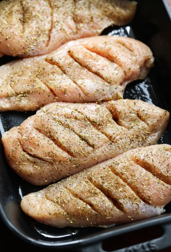 cut chicken breasts in a baking dish with itailan seasoning