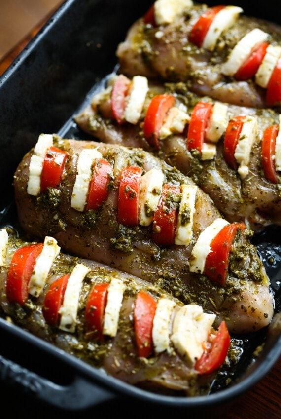 raw chicken breasts stuffed with tomato, mozzarella , and pesto in a baking dish