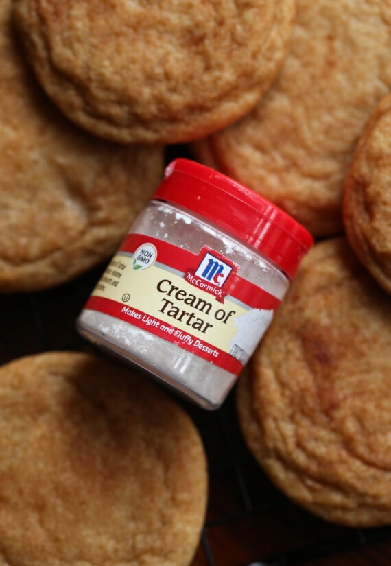 A container of cream of tartar on a rack of snickerdoodle cookies