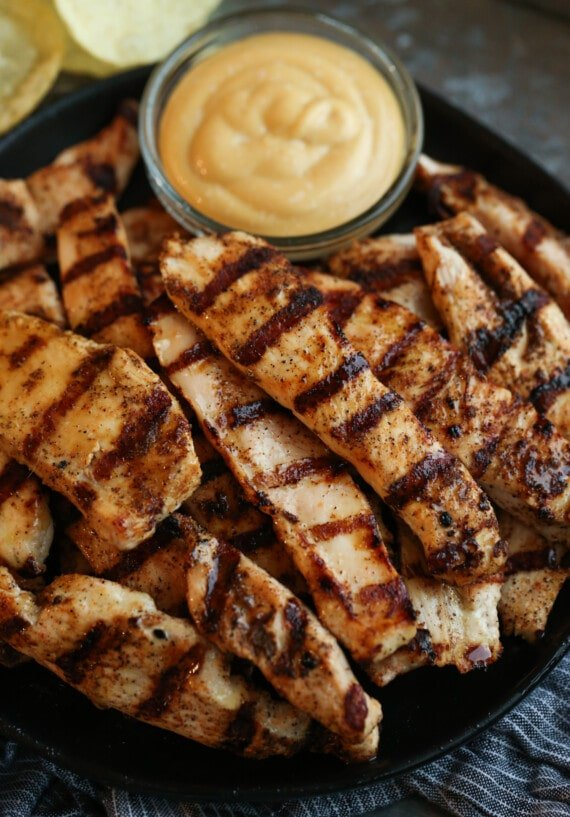 Grilled chicken tenders with a bowl of dip.