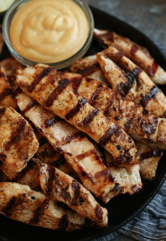 Plate of grilled chicken tenders with chicken dipping sauce.