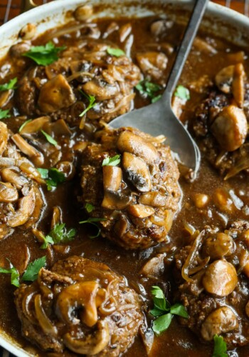 Easy Salisbury Steak recipe in a skillet with brown gravy, onions and mushrooms