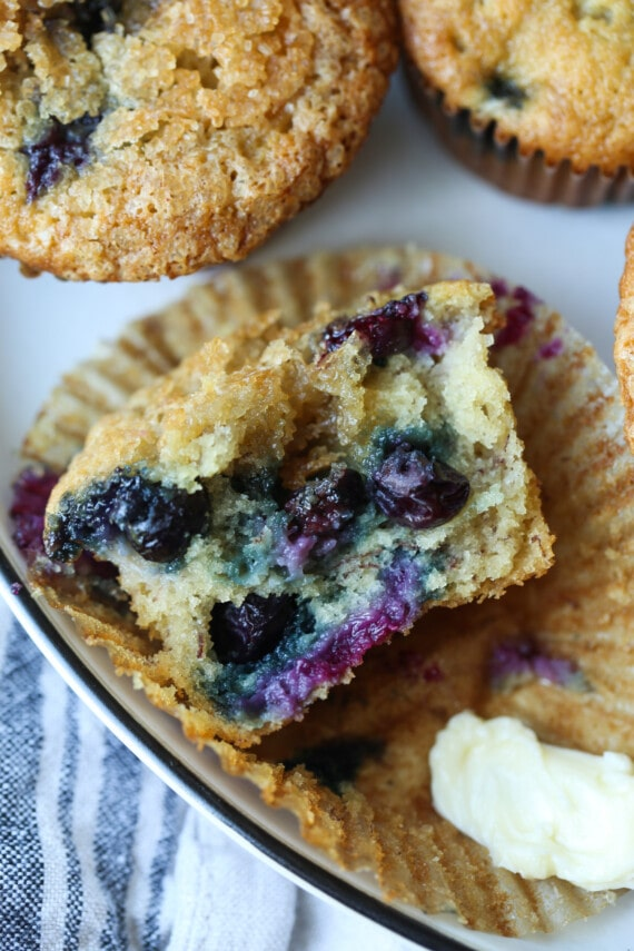 Half of a muffin with fresh blueberries in it.