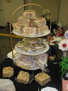 A Craft Fair Dessert Stand Holding Homemade Cookies and Rice Krispie Treats