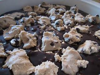 Brownie batter in a pan with chunks of raw chocolate chip cookie dough on top