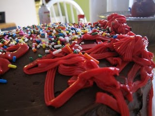 A birthday cake decorated with chocolate frosting, sprinkles and red frosting